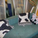 The sofa with cow-print blankets and toys